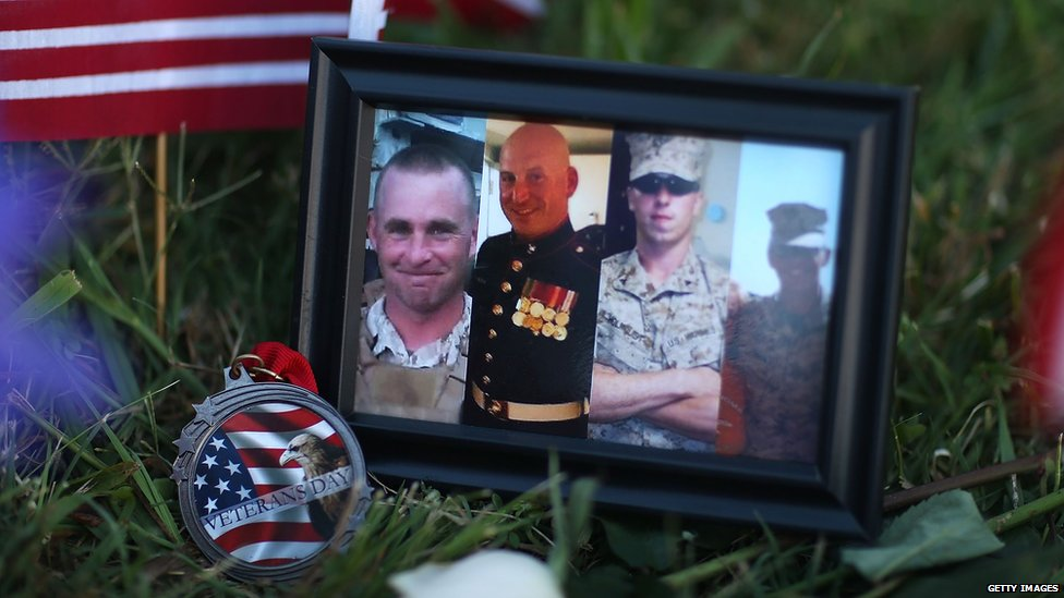 A photograph of other four victims of the shooting is seen among the memorial set up in front of the Armed Forces Career Center/National Guard Recruitment Office in Chattanooga, Tennessee on Saturday