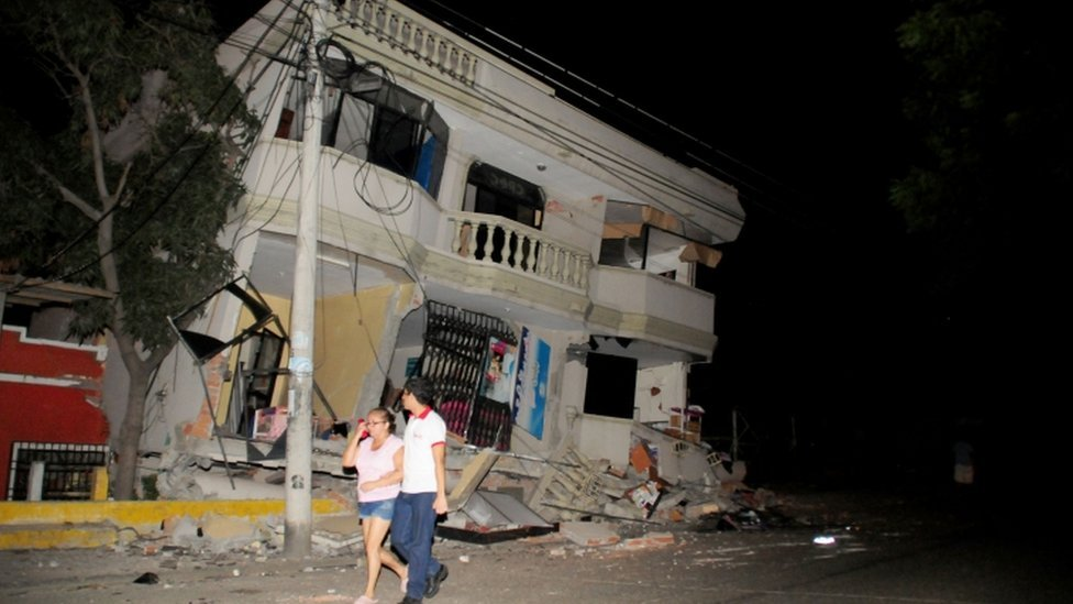 Residents walk on a street amid destroyed buildings following an earthquake, Guayaquil, Ecuador