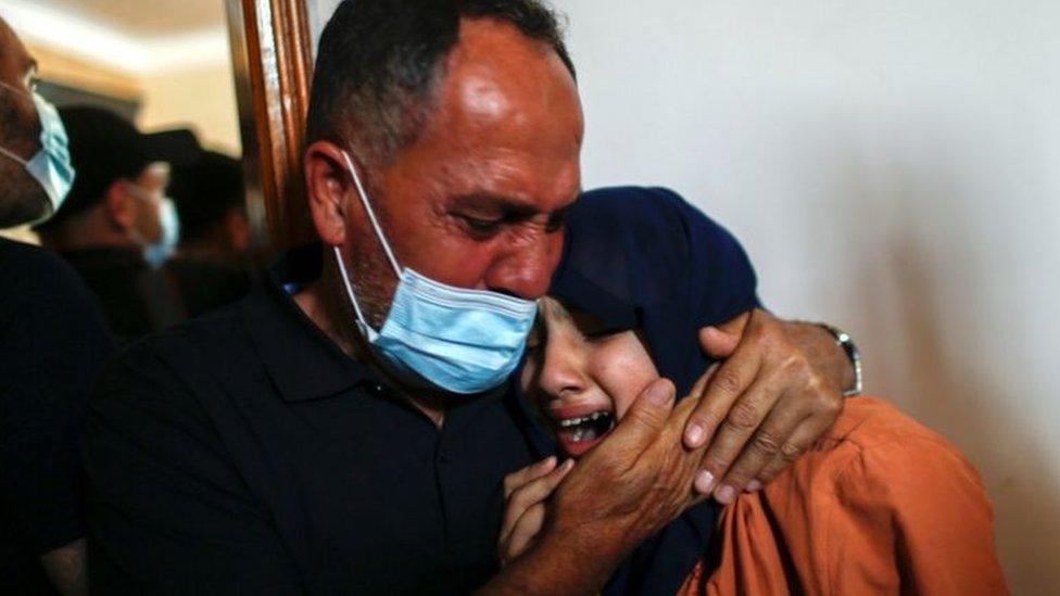 فلسطيني وعائلته يبكون قتلى سقطوا في غزة