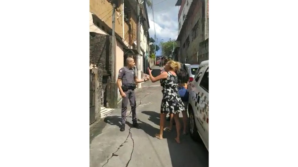 Ana-Paula talks to a policeman as blood runs down a street