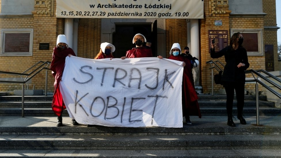 "Protesters hold a banned saying ""women's strike"" outside a cathedral in Lodz, Poland"