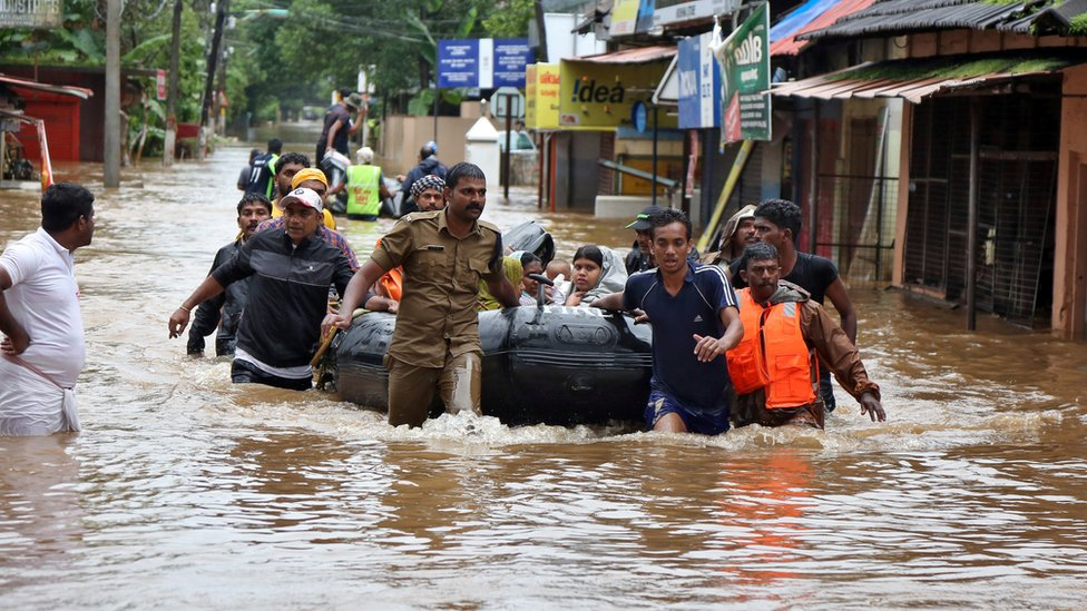 Rescuers evacuate people from a flooded area to a safer place in Aluva - 18 August