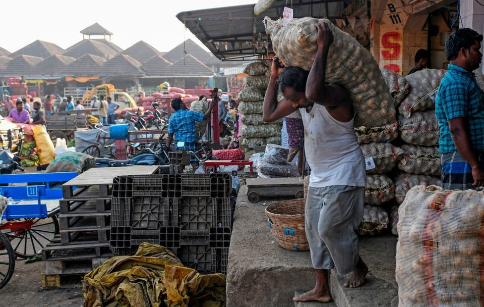 Labourers carry vegetable bags as farmers and traders negotiate prices at a wholesale vegetable market in Chennai.