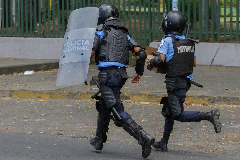 Policías corriendo en la calle