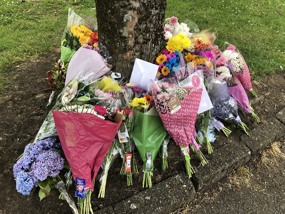 floral tributes at site of alleged hit and run
