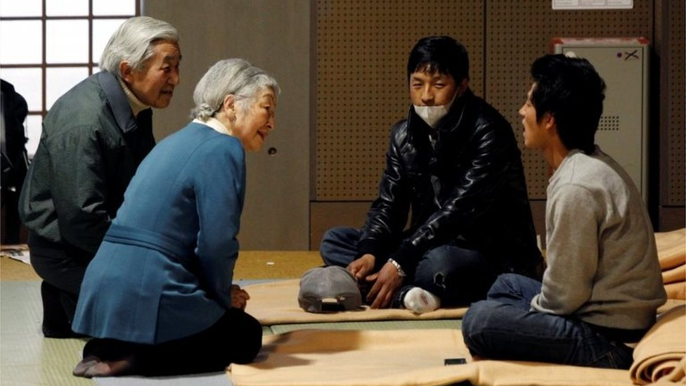 Japan's Emperor Akihito (L) and Empress Michiko (2nd L) talk with evacuees from the March 11 earthquake and tsunami