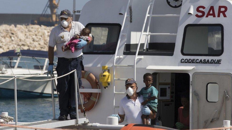 Children are brought ashore on an Italian coast guard boat at Pozzallo, Sicily, 15 July 2018