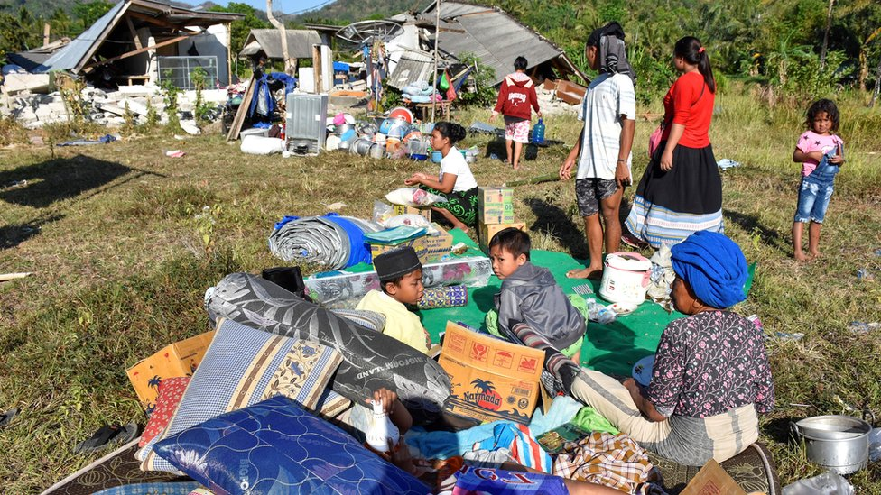 Residents sit outside their home with their belongings following a strong earthquake in Pemenang, North Lombok