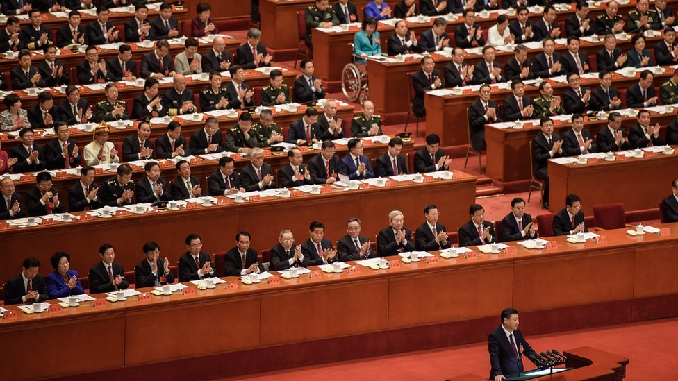 Delegates applaud a speech by President Xi Jinping at China's Communist Party Congress in Beijing. Most are men in dark suits, with a handful of women dotted around.