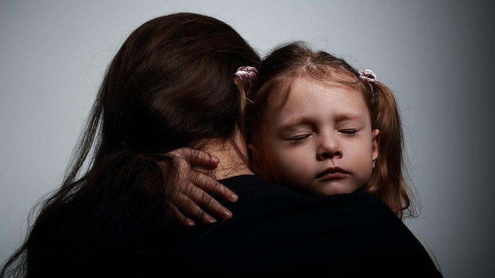 Una madre abrazando a su hija.