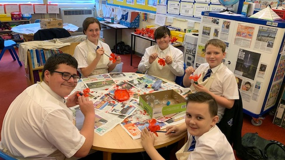 School children making poppies out of plastic bottles