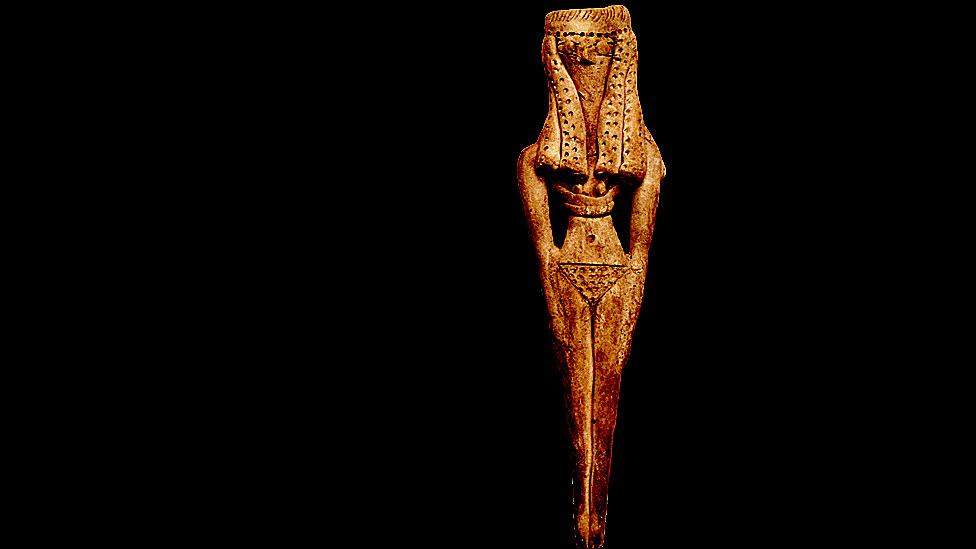 Una figura de fertilidad de una mujer, cuyo elaborado tocado, senos prominentes y pudendas resaltan su carácter erótico. Egipto antiguo. Reino Medio.