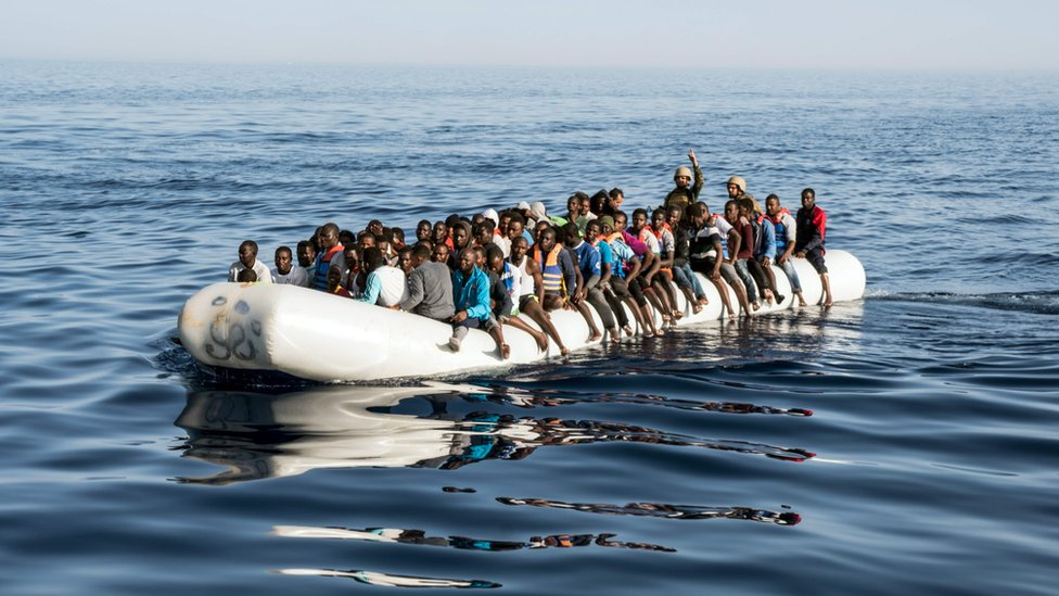 A picture taken on June 27, 2017 shows Libyan coast guardsmen standing in a dinghy carrying illegal immigrants during a rescue operation of 147 people who were attempting to reach Europe