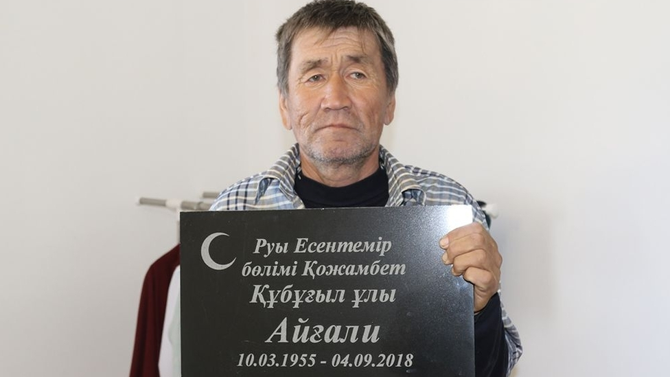 Esengali Supygaliev holds the headstone of his brother Aigali, Kazakhstan, 2018