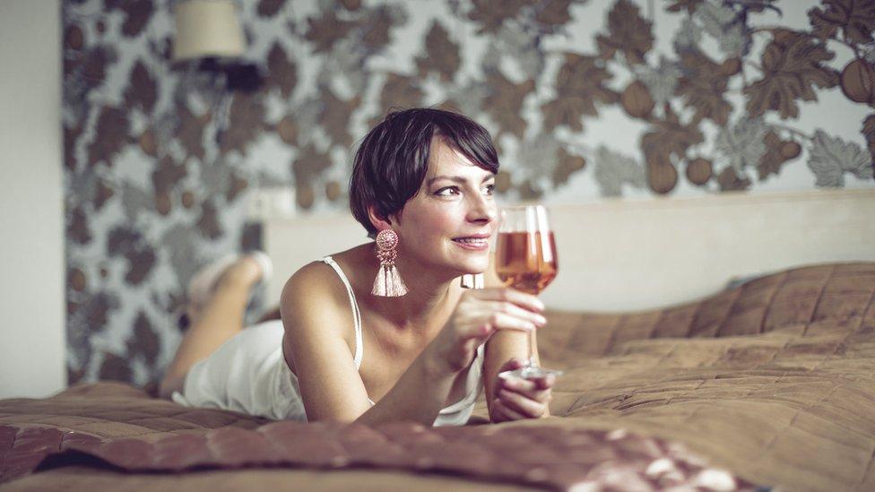 Mujer tomando en la cama y en ropa interior.