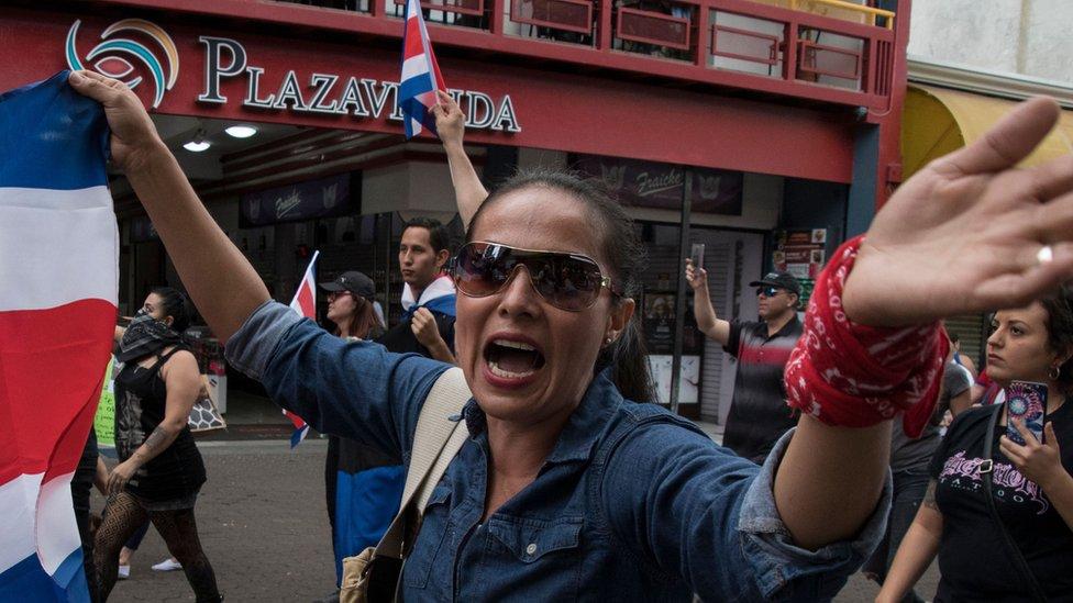 Una mujer con una bandera de Costa Rica en una marcha antiinmigrantes