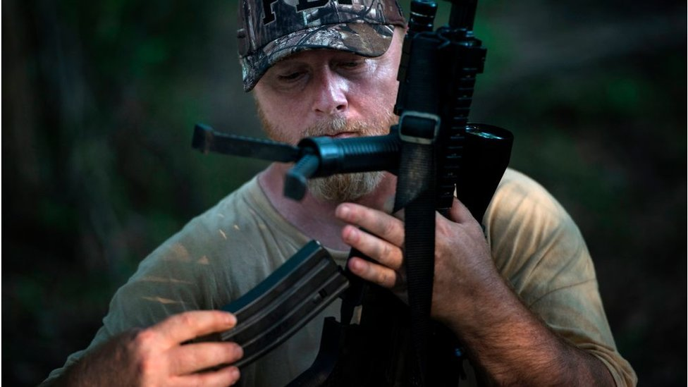 Chris Hill, founder of the Georgia Security Force III% militia, loads a rifle during a field training exercise July 29, 2017 in Jackson, Georgia