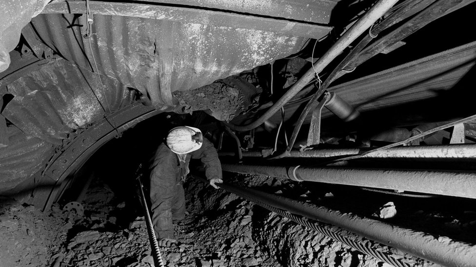A pit official at Sutton Colliery near Mansfield, Nottinghamshire, checks on a trunk conveyor at the coal face.