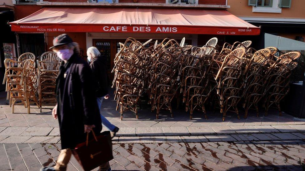 Pessoas caminhando em frente a bar fechado por confinamento na França