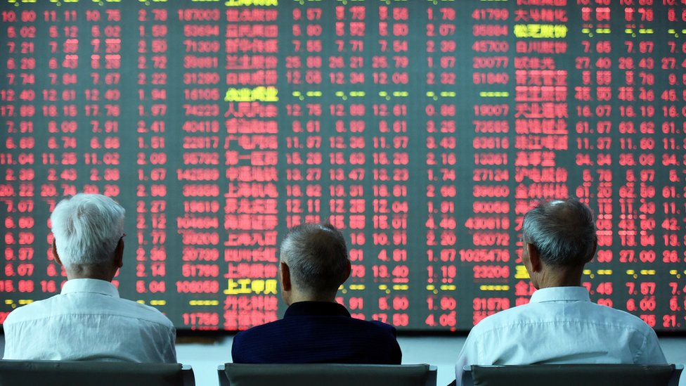 Chinese investors sit in front of a stock board