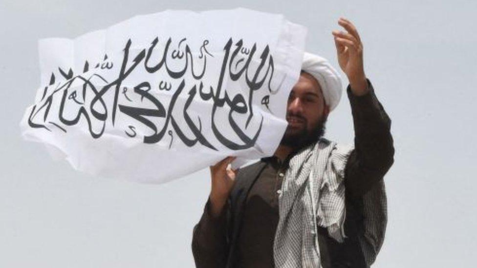 Un hombre afgano ondea la bandera del Talibán en la frontera con Pakistán, 17 de julio, 2021