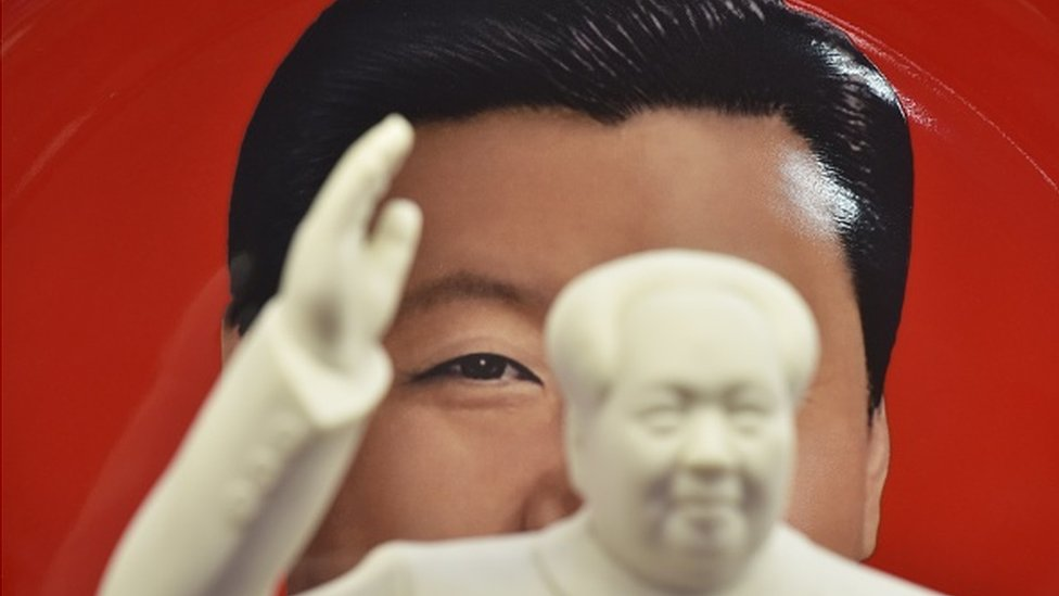 TOPSHOT - A decorative plate featuring an image of Chinese President Xi Jinping is seen behind a statue of late communist leader Mao Zedong at a souvenir store next to Tiananmen Square in Beijing on February 27, 2018. China's propaganda machine kicked into overdrive on February 27 to defend the Communist Party's move to scrap term limits for President Xi Jinping as critics on social media again defied censorship attempts. The country has shocked many observers by proposing a constitutional amendment to end the two-term limit for presidents, giving Xi a clear path to rule the world's second largest economy for life.