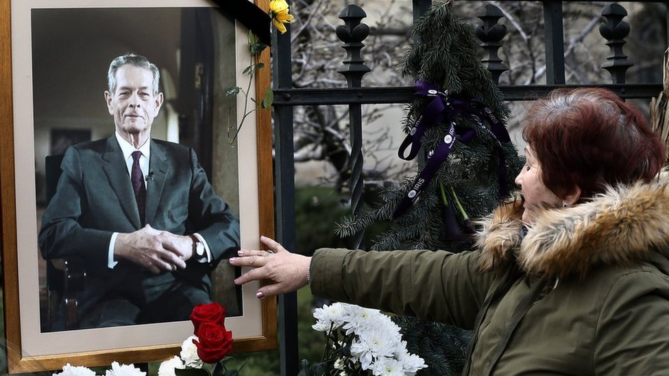 A Romanian woman closes her eyes while touching King Michael's portrait