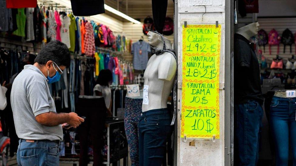 Un hombre, junto a un cartel con pecios en dólares en un comercio de Caracas.