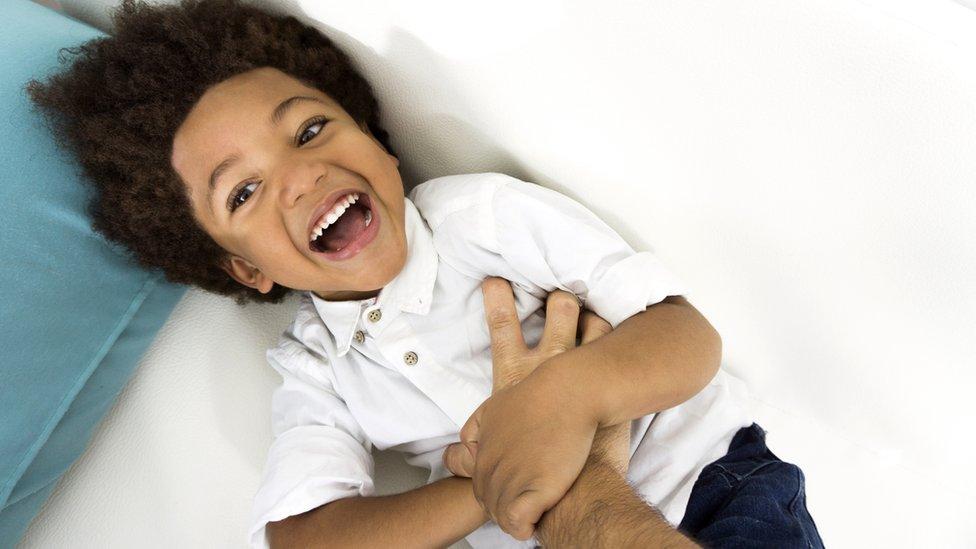 Niño de unos 6 años riéndose al recibir cosquillas.