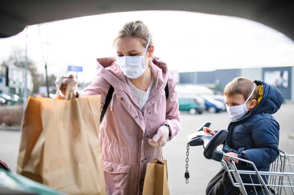 Mulher carrega compras no carro; uma criança pequena aguarda ao lado, sentada no carrinho
