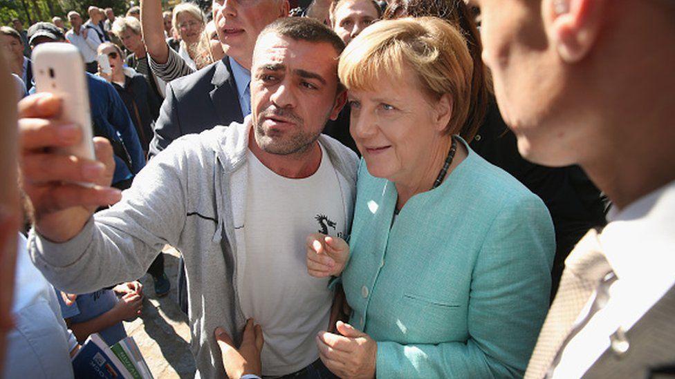 المستشارة الألمانية أنغيلا ميركل بين جمع من المهاجرين، تلتقط صورة مع أحدهم