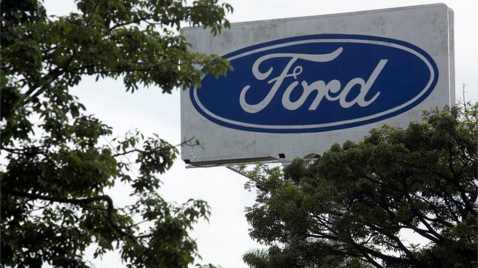 Outdoor com logotipo da Ford em meio a árvores