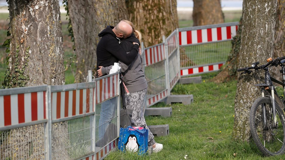 A couple hug as they stand on both sides of a fence built by German authorities on the German-Swiss border on 20 March