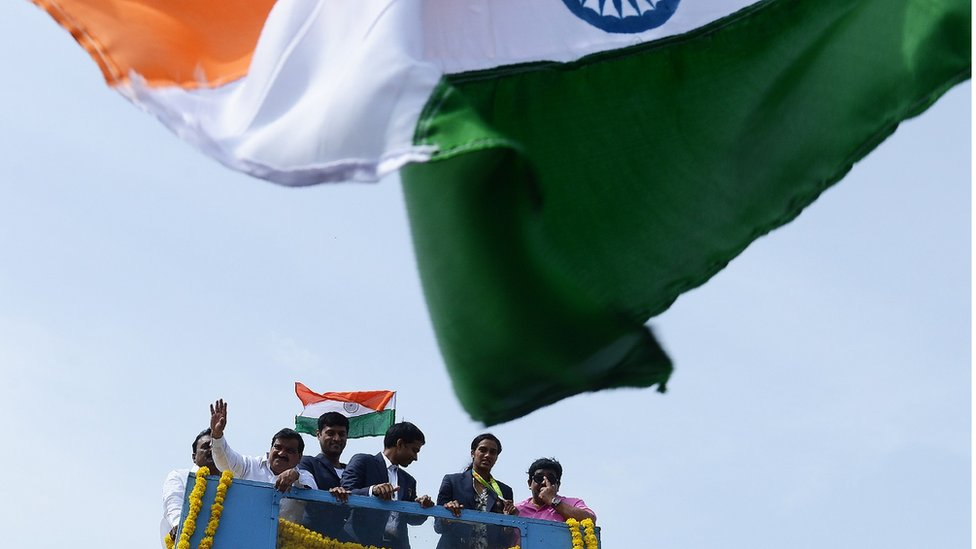 Indian badminton player and Olympic silver medalist P.V Sindhu (2R) and her coach P. Gopichand (C) take part in a parade after arriving home from the Rio Olympics in Hyderabad on August 22, 2016. India swelled with pride August 20 after badminton champion P.V. Sindhu became the first woman in the country's history to win an Olympic silver medal. /