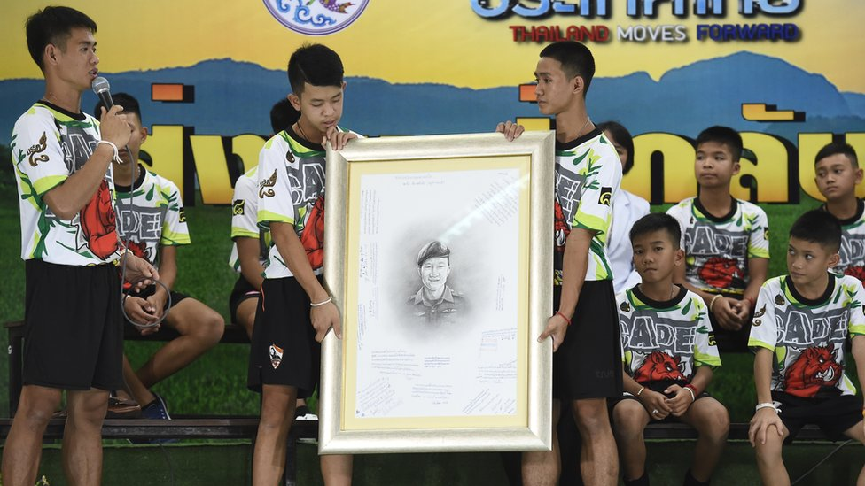 Rescued Thai football coach Ekkapol Chantawong (left) together with 12 children pays tribute to Saman Gunan during a press conference in Chiang Rai, 18 July 2018