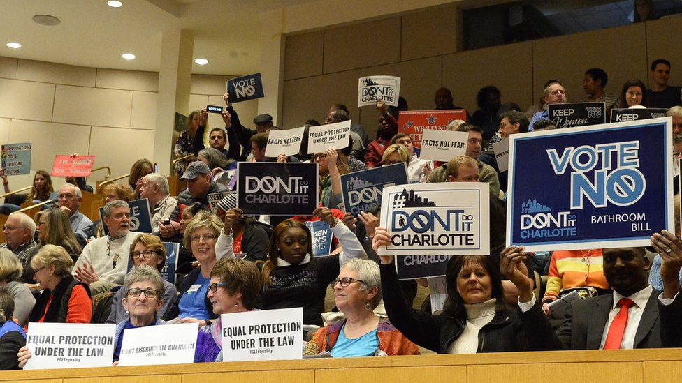 Audience holds up signs at ordinance debate