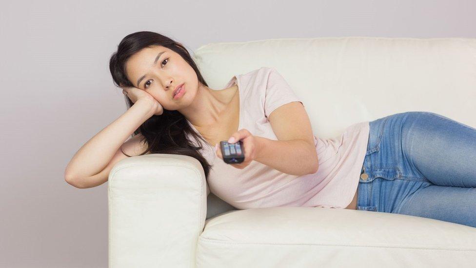 Una mujer en un sofá con un control remoto en la mano.