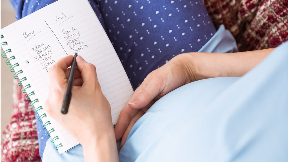 pregnant woman holding page with list of baby names