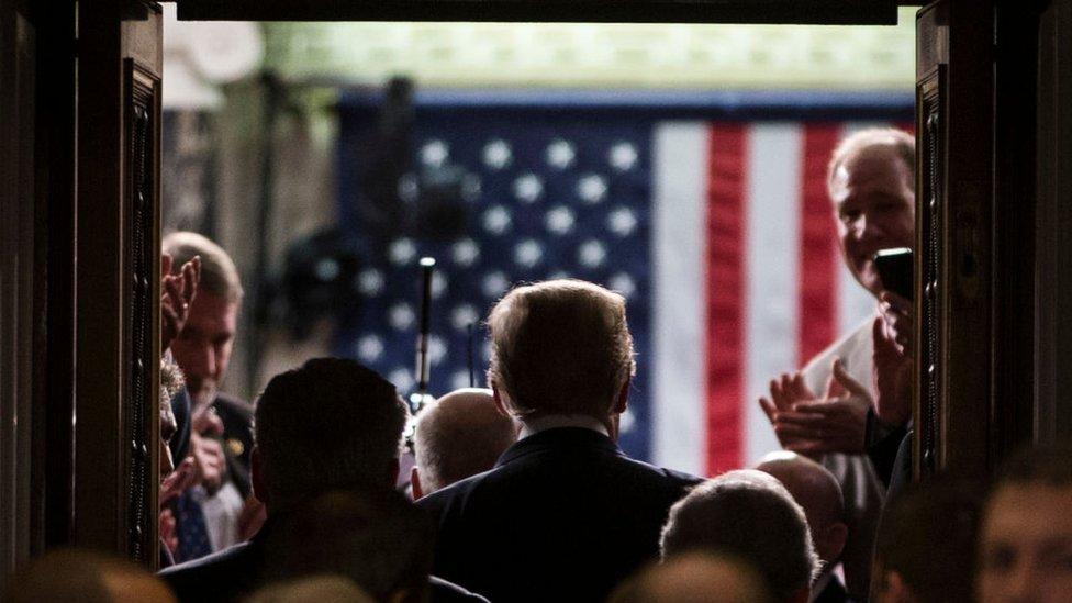 Trump de espaldas entrando a la sala