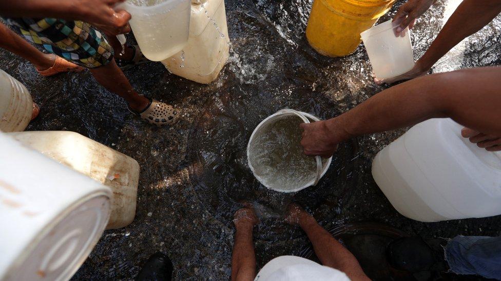 Gente recogiendo agua.