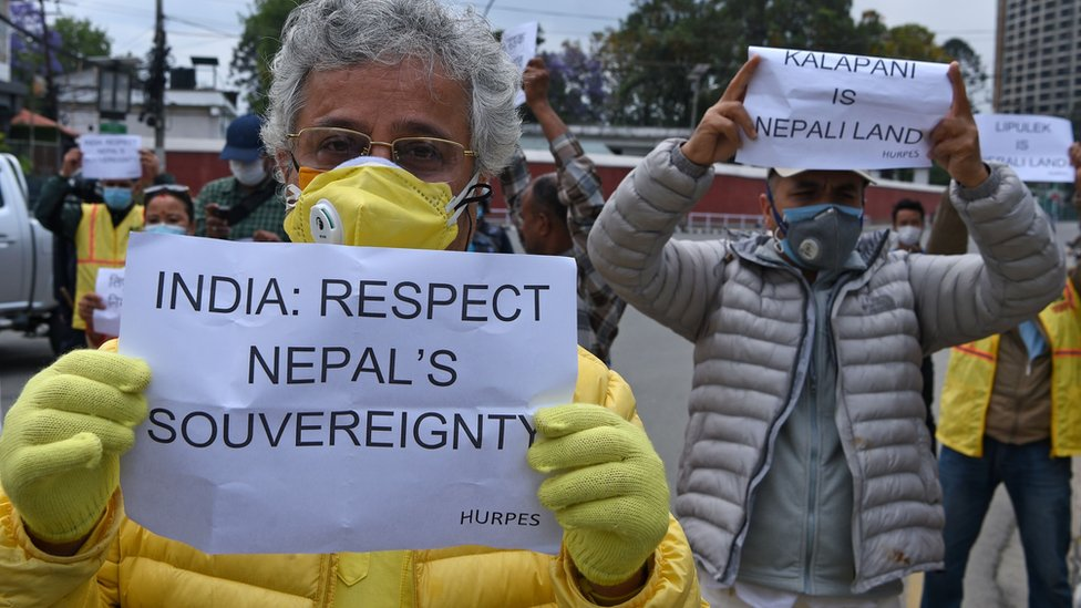Human rights activists hold placards during a protest against India's newly inaugurated link road to the Chinese border, near Indian embassy in Kathmandu on May 12, 2020.