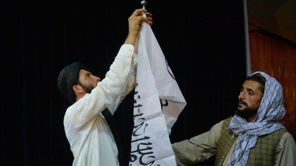 Dos talibanes instalan una bandera en Kabul.