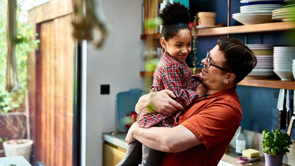 Hombre cargando a niña en sus brazos