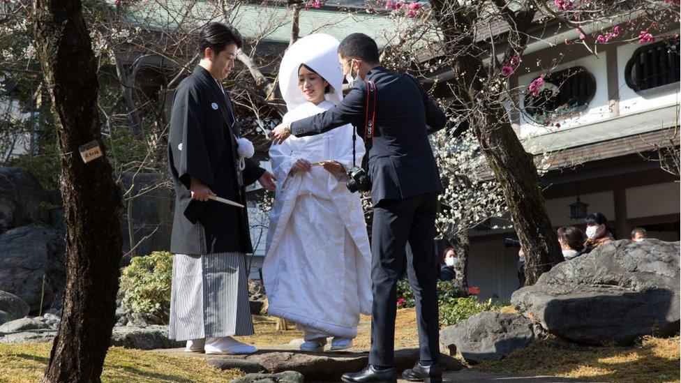 Pareja de recién casados tomándose fotos en Tokio.