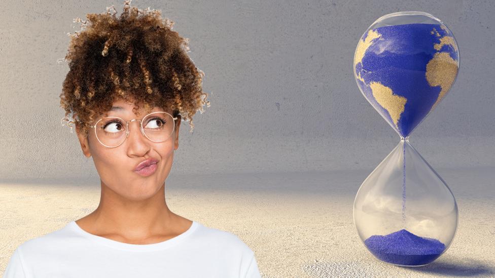 Una mujer mira con sospecha un reloj de arena con el mapa dentro