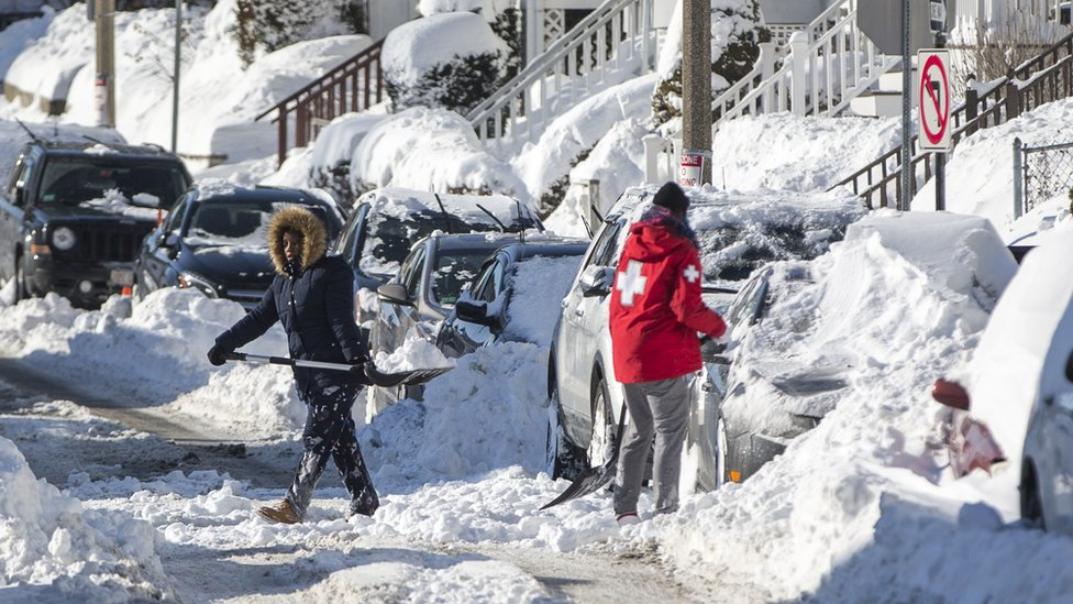 "Residents shovel snow on a street in a neighbourhood of Boston, Massachusetts, a day after the region was hit with a ""bomb cyclone"", 5 January 2018"