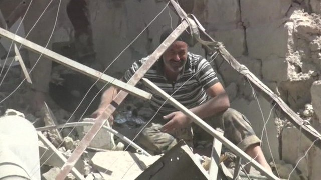 A man sifts through rubble in Aleppo Syria