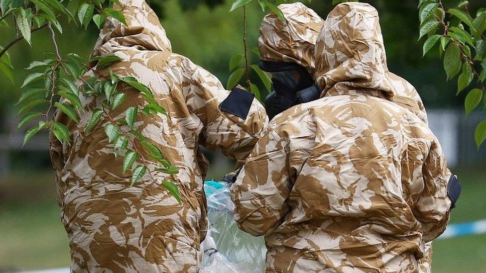 People in military hazardous material protective suits collect an item in Queen Elizabeth Gardens in Salisbury
