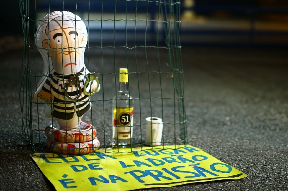 """Pictured: A balloon depicting Lula as an immate, and a sign reading """"Lula, the place for a thief is prison."""""""