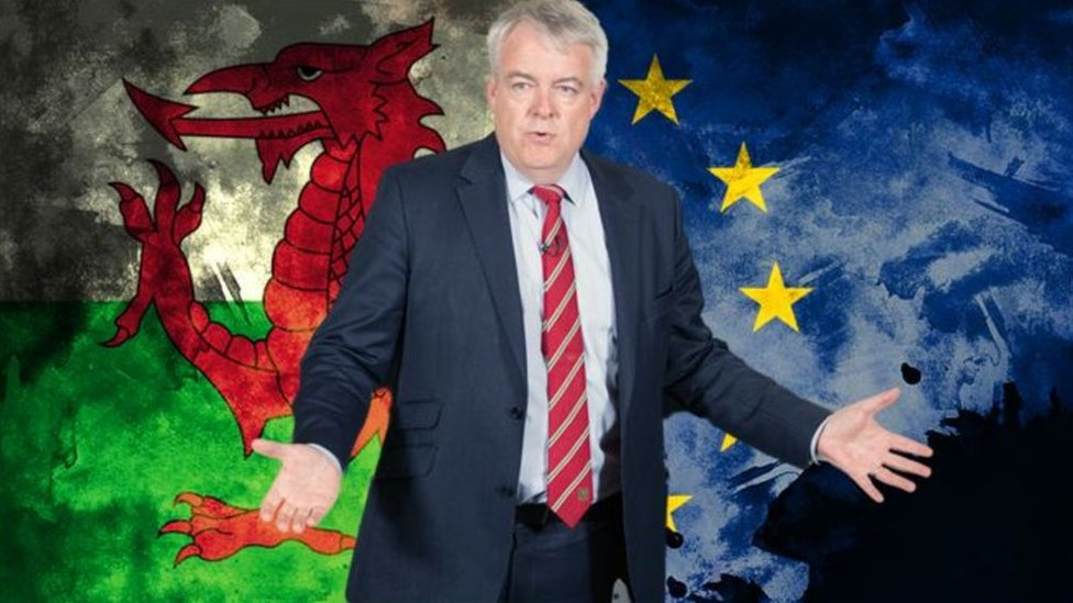 Carwyn Jones with a Wales and EU flag graphic behind him
